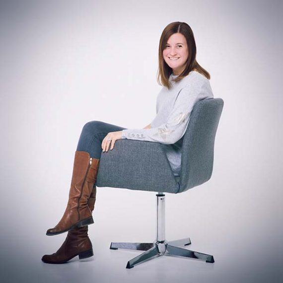 A smiling girl while sitting on a grey swivel chair with her body turned sideways.